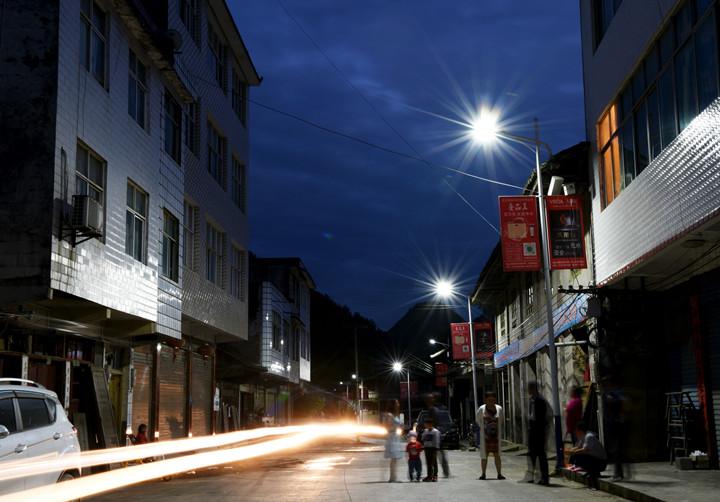 6月30日晚上8點,通過慈善眾籌項目援建的老里壩集鎮路燈準時點亮,村民在路燈下乘涼聊天。( 李維君  攝)_副本.jpg