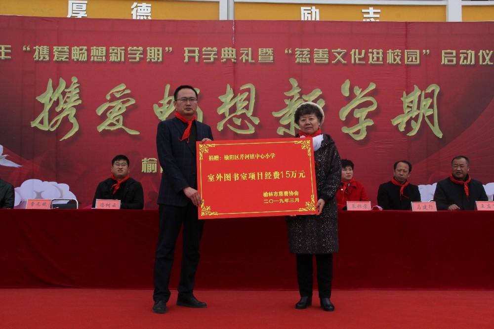 榆林市慈善協會副會長兼項目部部長龐瑤向芹河中心小學遞交捐贈牌.JPG