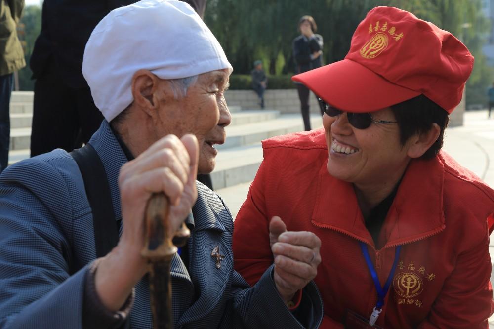 在2014年重阳节敬老活动中,慈善志愿者同参加活动的老人热情交谈.JPG